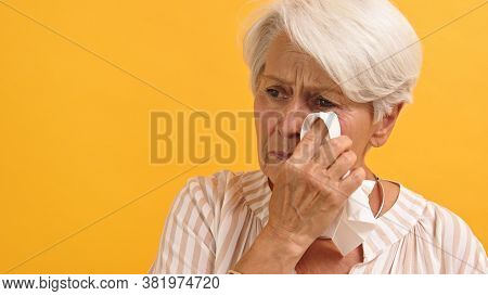 Portrait Of Sad Vulnerable Old Woman Wiping Her Tears. Isolated On The Orange Background. High Quali