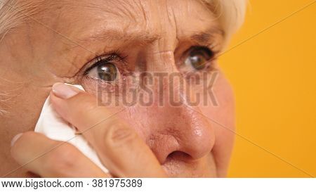 Close Up Of Sad Vulnerable Old Woman Wiping Her Tears. High Quality Photo