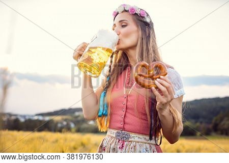 Woman in traditional clothing enjoying drinking beer in Bavaria