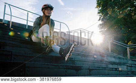 Young Sporty Woman Adjusting Rollerblades While Sitting On The Stairs In The Skatepark. . High Quali