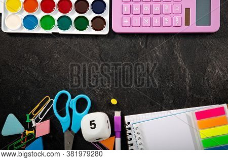 Back To School Background With Accessories For The Schoolroom. Paints On Black Textural Background.