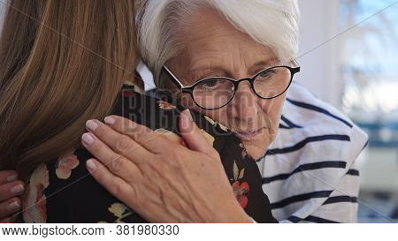 Young Woman Embracing An Elderly Lady. Grief And Bead News, Empathy Concept. High Quality 4k Footage