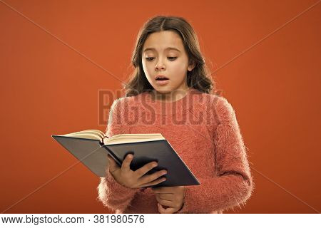 Reading Practice For Kids. Childrens Literature. Girl Hold Book Read Story Over Orange Background. C