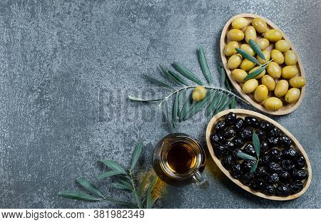 Glass Bottle Of Homemade Olive Oil And Olive Tree Branch, Raw Turkish Green And Black Olive Seeds An