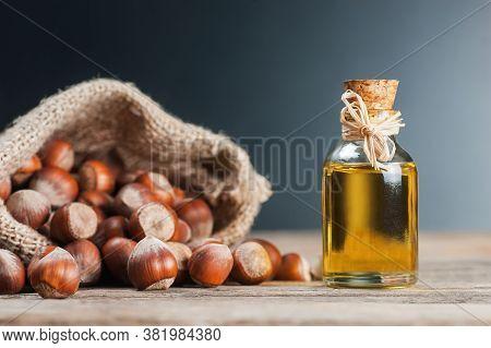 Hazelnuts, Filbert In Burlap Sack And Hazelnut Oil In Glass Of Bottle On Wooden Backdrop. Heap Or St