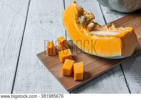 Sliced And Chopped Pumpkin Pieces. Pumpkin With Seeds. Pumpkin Chunks On Wooden Background. Fresh An