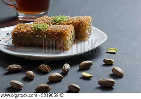 Turkish Famous Dessert Burma Kadayif On Plate With Pistachio Nuts Near Glass Of Turkish Tea, Shredde