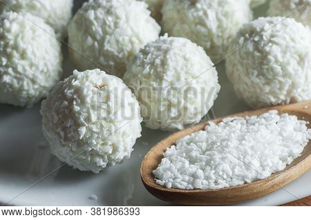 White Chocolate Ball Candy With Coconut Topping And Coconuts In Wooden Spoon. Coconuts Pastry Concep