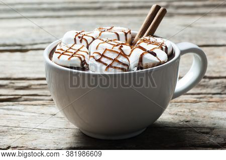 Hot Chocolate With Cinnamon Sticks And Marshmallow Candies With Chocolate Sauce In White Ceramic Mug