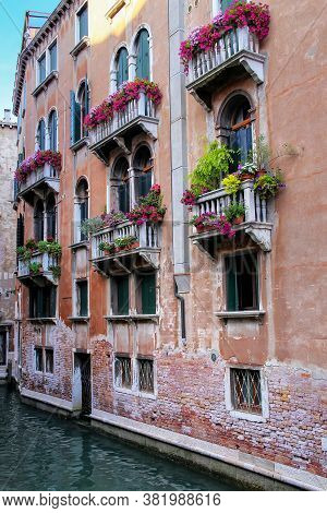 Building With Flower Boxes On The Balconies In A Narrow Canal, Venice, Italy. Venice Is Situated Acr