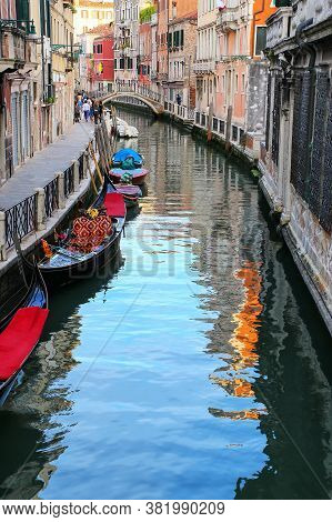 Narrow Canal Lined With Gondolas In Venice, Italy. Venice Is Situated Across A Group Of 117 Small Is
