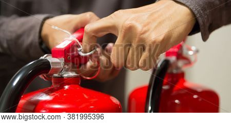Fire Protection Engineer Check The Safety Pin Of Red Fire Extinguishers Tank At The Exit Door In The