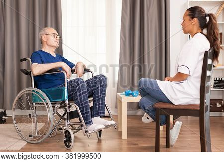 Old Man And Assistant Discussing About His Accident And Treatment. Disabled Disability Old Person Wi