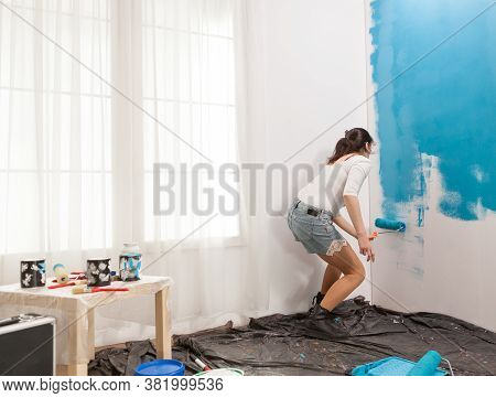 Young Housewife Painting Wall With Roller Brush While Renovating His Apartment. Handyman Redecoratio