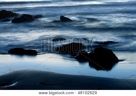 Silhouette Of Rock Detail And Beach At Sunset