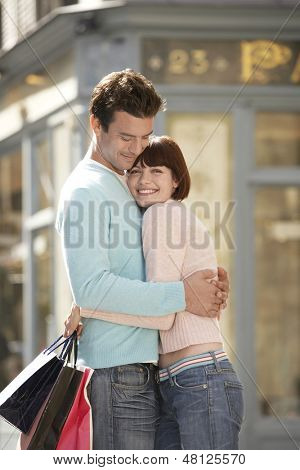 Side view of a couple with shopping bags embracing on the street