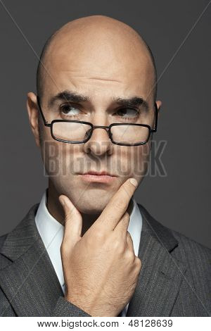 Closeup of a bald businessman wearing glasses with hand on chin against gray background