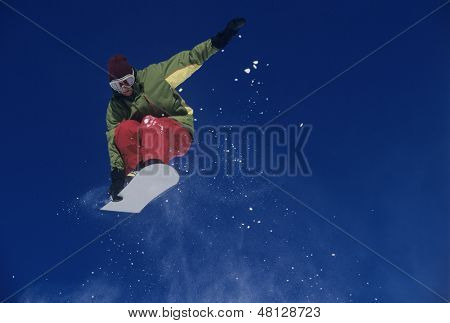 Low angle view of a male snowboarder jumping with snowboard against blue sky