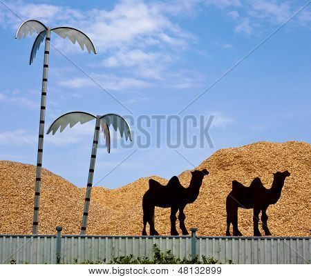 Clipped Camel Silhouettes And Metal Palms At Sawdust Storage Fence