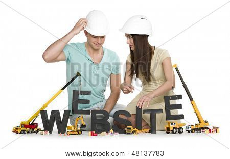 Website under construction concept: Inquiring man and woman building the word website along with construction machines, isolated on white background.