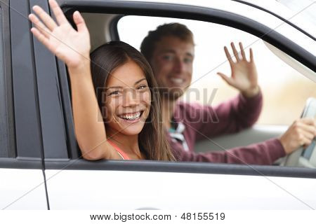 Drivers driving in car waving happy at camera. Young couple on road trip in new car. Interracial happy couple.