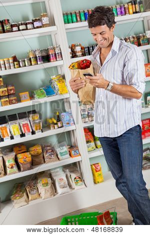 Mid adult male customer with grocery bag checking list in supermarket