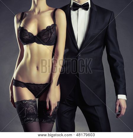 Art photo of a young couple in sensual lingerie and a tuxedo poster