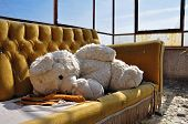 Vintage teddy bear and couch in abandoned building. Social issues. poster