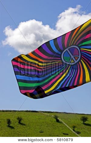 Pretty colored flag against a blue sky with farm land