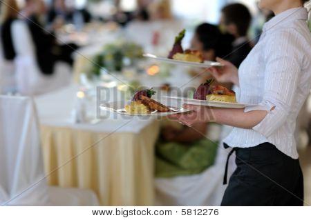 Kellnerin mit drei Platten
