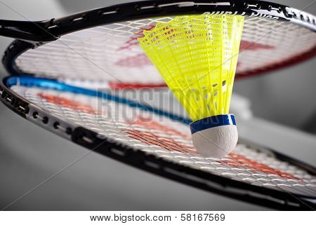 Badminton rackets and colorful yellow shuttlecock - closeup