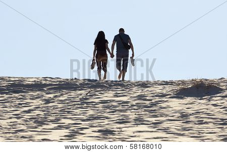 Young Couple Walks On Sand Dune. Fingal Bay. Port Stephens. Australia.