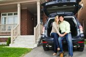 Happy young couple sitting at back of car on driveway poster