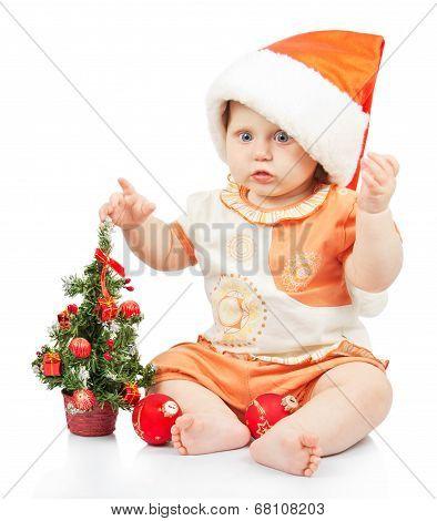 Beautiful baby in santa hat near christmas tree