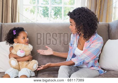 Pretty mother sitting on couch with petulant daughter at home in the living room
