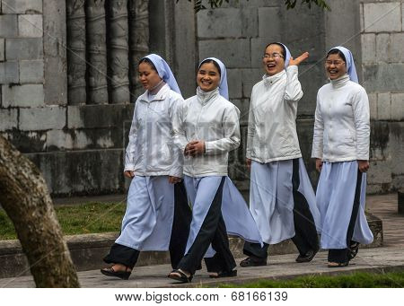 Four Young Vietnamese Nuns In Ao Dai Going To Church Service.