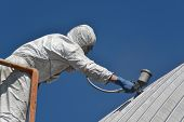 Tradesman spray painting the roof of an industrial building poster