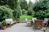 Backyard patio and garden furniture in an English home poster