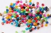 An array of children's coloured plastic beads on white background. poster