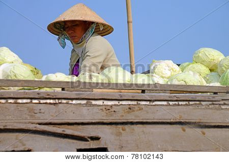 Woman selling cabbages at the floating market, in Can Tho, Vietnam