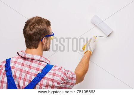 Repairman painting wall by roller