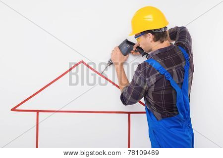 Young repairman standing near pictured house with drill. Concept for finishing repair poster