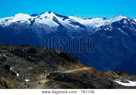 People, path & snow peaks