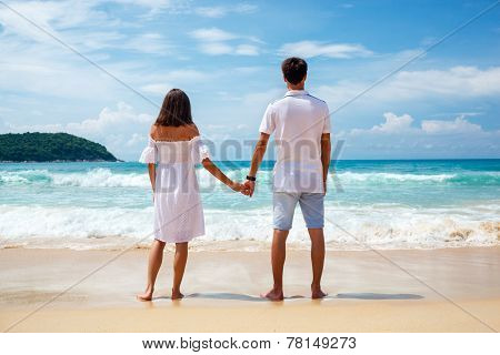 Back view of young couple standing on sandy beach
