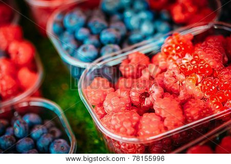 Baskets Full Of Raspberries And Blueberries On The Farmers Market