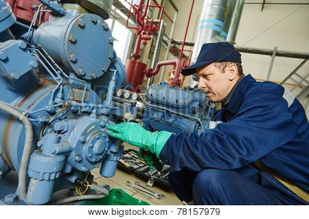 service engineer worker at industrial compressor refrigeration station repairing and adjusting equipment at manufacturing factory poster