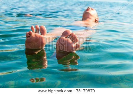 feet with splayed fingers lying on the water man poster