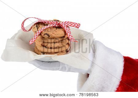 Santa Claus holding a plate with a stack of chocolate chip cookies tied with a ribbon. Only Santa's gloved hand and red sleeve are shown as he holds the plate over a white background.