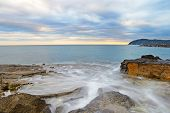 Blurred seascape long exposure taken on the rocky coastline of San Bartolomeo al Mare at dusk Liguria Italy. poster