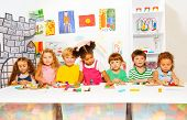 Big group of diverse looking preschool boys and girls play with modeling clay in class in kindergarten poster